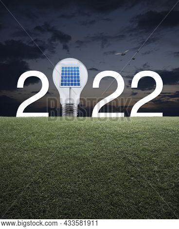 2022 White Text And Light Bulb With Solar Cell Inside On Green Grass Field Over Sunset Sky With Bird