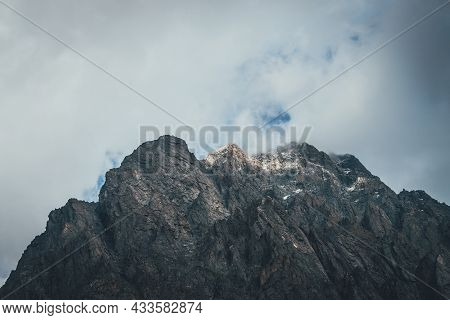 Atmospheric Mountain Landscape With Low Cloud On Mountain Top In Sunlight. Dark Rocks With Snow And