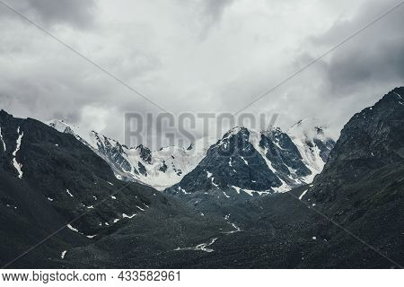 Dark Atmospheric Mountain Landscape With Glacier On Black Rocks In Gray Cloudy Sky. Snowy Mountains