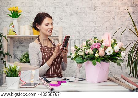 Young Woman Florist At Work. Business Woman Sale And Floristry Concept Happy Smiling Woman Making Bu