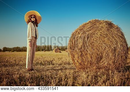 Full length portrait of an elegant fashion model in a knitted sweater, wide-brimmed straw hat and round glasses posing by a haystack in the light of the setting sun. Modern boho style.