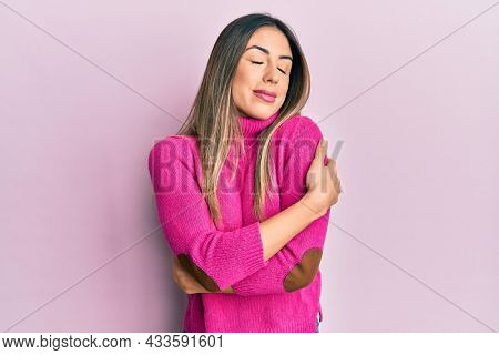 Young hispanic woman wearing casual clothes hugging oneself happy and positive, smiling confident. self love and self care