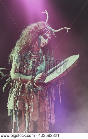 Authentic shamanic woman in ethnic dress and deer antlers headdress playing on shaman frame drum on a dark background with a mystical haze. Ethnic traditions. Paganism. Halloween.