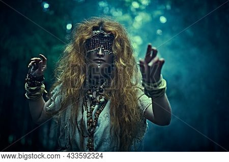 A frightening forest witch with a mask covering her eyes stands in a gloomy forest and holds out her arms forward. Woman shaman. Paganism. Death ritual. Halloween.
