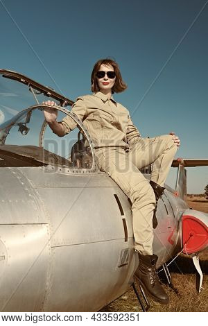 Full length portrait of a beautiful woman pilot wearing uniform and sunglasses leaning to her fighter jet at the airfield. Military aircraft.