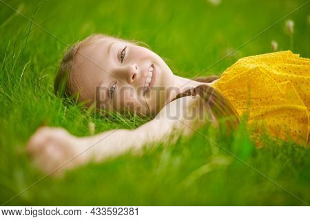 Cute little girl with pigtails lying on a green lawn happily smiling. Summer park background. Happy summer days. Rest in the park.