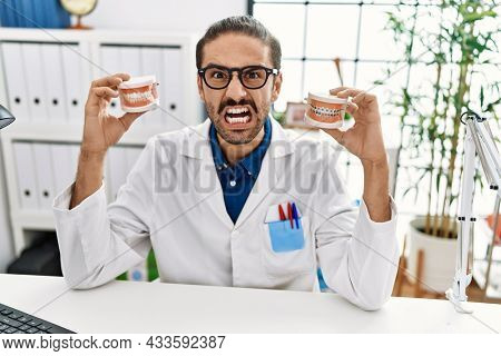 Young hispanic dentist man holding denture with orthodontic braces angry and mad screaming frustrated and furious, shouting with anger. rage and aggressive concept.