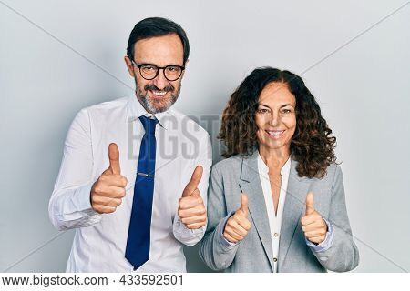 Middle age couple of hispanic woman and man wearing business office uniform success sign doing positive gesture with hand, thumbs up smiling and happy. cheerful expression and winner gesture.