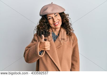 Middle age hispanic woman wearing french look with beret doing happy thumbs up gesture with hand. approving expression looking at the camera showing success.