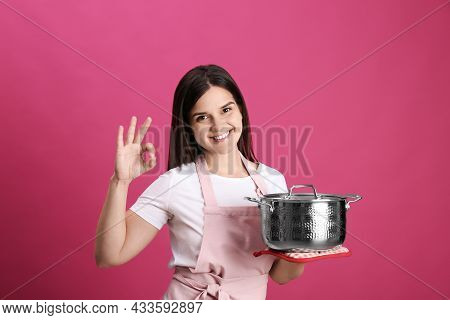 Happy Young Woman With Cooking Pot On Pink Background