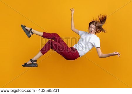 Studio Shot Of Young Cute Girl Isolated Falling Down Isolated On Yellow Color Studio Background. Con