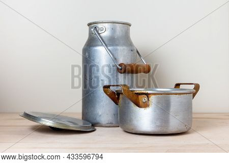 Old Aluminum Crockery On The Kitchen Shelf. Milk Can And Vintage Pot With Curved Lid. Still Life In