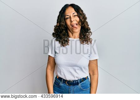 Middle age hispanic woman wearing casual white t shirt sticking tongue out happy with funny expression. emotion concept.