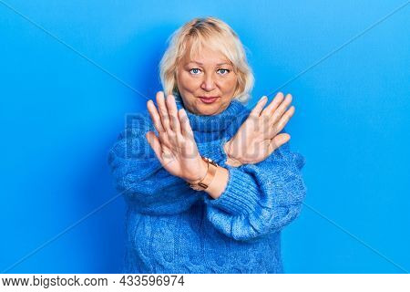 Middle age blonde woman wearing casual clothes rejection expression crossing arms and palms doing negative sign, angry face