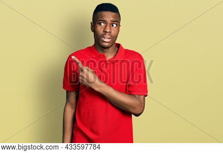 Young african american man wearing casual red t shirt pointing aside worried and nervous with forefinger, concerned and surprised expression