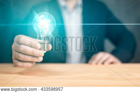 Innovative Idea In Businessman Hand. Hand Holding Light Bulb On Wood Table. Concept Of Inspiration C