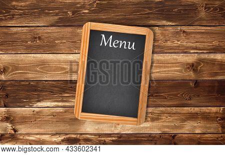 Aged  Menu Blackboard  On A Wooden Wall