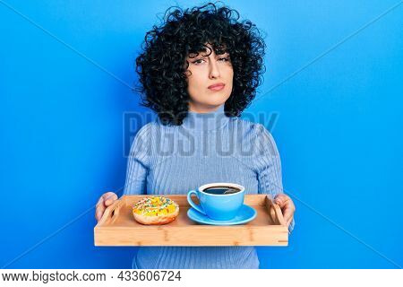 Young middle east woman holding tray with doughnut and cup of coffee skeptic and nervous, frowning upset because of problem. negative person.
