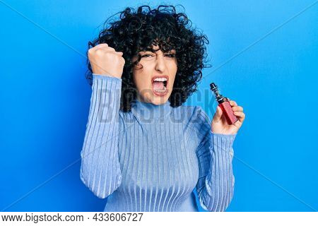 Young middle east woman holding electronic cigarette annoyed and frustrated shouting with anger, yelling crazy with anger and hand raised