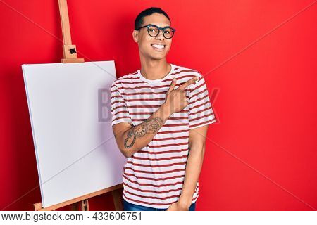 Young african american guy standing by painter easel stand smiling cheerful pointing with hand and finger up to the side
