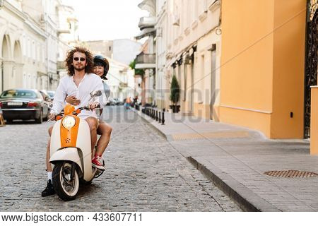 Happy young multiethnic couple on scooter enjoying ride on a street