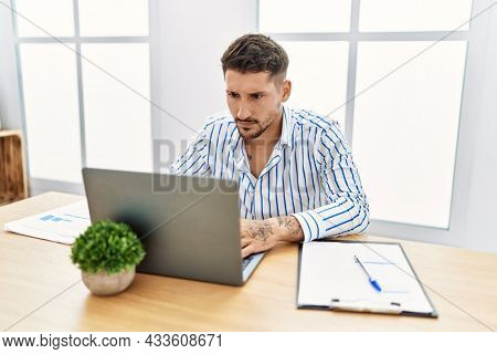 Young handsome man with beard working at the office using computer laptop skeptic and nervous, frowning upset because of problem. negative person.