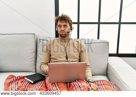 Young handsome man with beard wearing operator headset working from home puffing cheeks with funny face. mouth inflated with air, crazy expression.