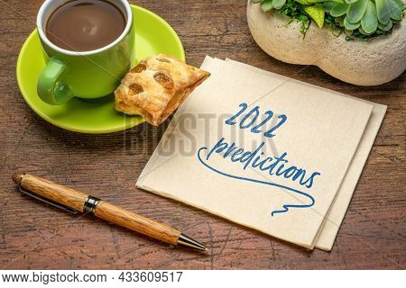 2022 predictions - handwriting on a napkin with a cup of coffee, business and financial trends and expectations in New Year