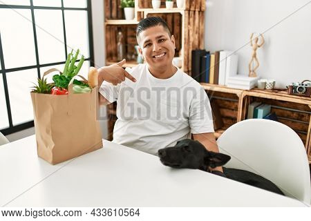 Young hispanic man sitting with paper bag with groceries pointing finger to one self smiling happy and proud
