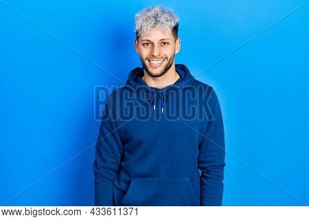 Young hispanic man with modern dyed hair wearing casual blue sweatshirt with a happy and cool smile on face. lucky person.