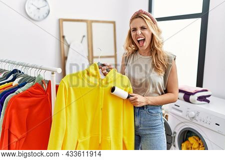 Beautiful blonde woman at laundry room cleaning clothes with pet hair remover roller angry and mad screaming frustrated and furious, shouting with anger. rage and aggressive concept.