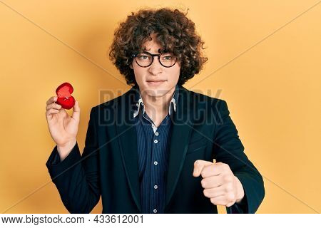 Handsome young man holding engagement ring for proposal annoyed and frustrated shouting with anger, yelling crazy with anger and hand raised