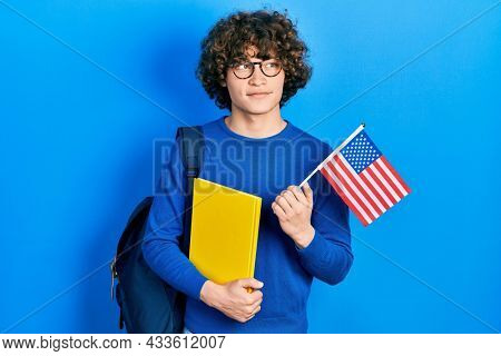 Handsome young man exchange student holding usa flag smiling looking to the side and staring away thinking.