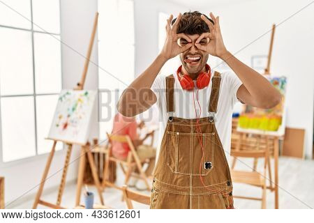 Young hispanic man at art studio doing ok gesture like binoculars sticking tongue out, eyes looking through fingers. crazy expression.