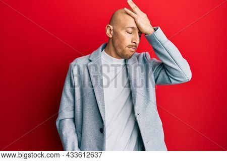 Bald man with beard wearing business jacket surprised with hand on head for mistake, remember error. forgot, bad memory concept.