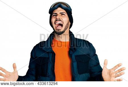 Young hispanic man with beard wearing snow wear and sky glasses crazy and mad shouting and yelling with aggressive expression and arms raised. frustration concept.