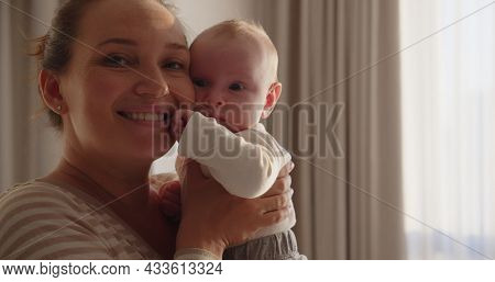 Young happy  mother  holds her newborn baby, window with sunset behind on a background. Closeup portrait of a loving mother with a child. Happy mom with her  infant son. Mum loves of her infant child