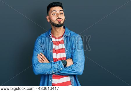 Young hispanic man with beard with arms crossed gesture looking at the camera blowing a kiss being lovely and sexy. love expression.