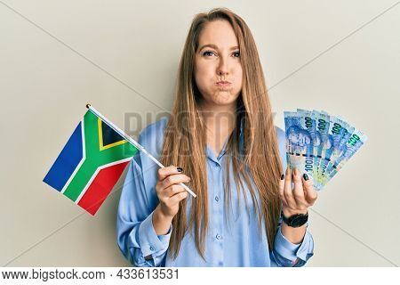 Young blonde woman holding south african flag and rands puffing cheeks with funny face. mouth inflated with air, catching air.