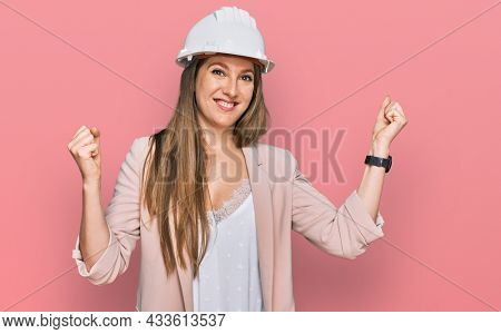 Young blonde woman wearing architect hardhat screaming proud, celebrating victory and success very excited with raised arms