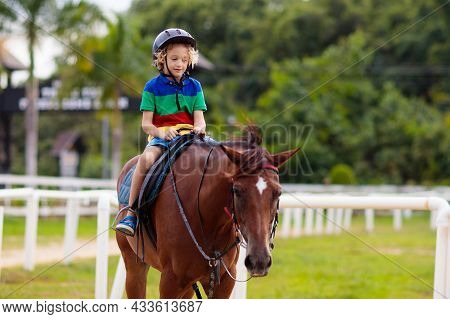 Kids Ride Horse. Child On Pony In Tropical Resort. Horseback Riding Lesson For Young Jockey In Eques