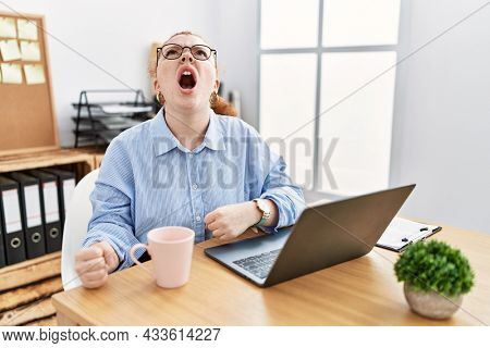 Young redhead woman working at the office using computer laptop angry and mad screaming frustrated and furious, shouting with anger. rage and aggressive concept.