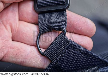 On The Fingers On The Hand There Is A Black Metal Fastening Ring On The Black Harness Of The Backpac