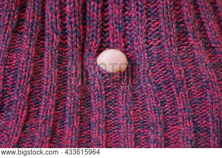 One White Finger In A Hole In Torn Red Woolen Fabric Of Old Clothes