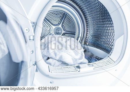 Inside of tumble dryer with clean white towels - new generation of dryer,  household concept