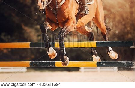 A Bay Racehorse With A Rider In The Saddle Jumps Over A High Yellow-black Barrier At A Show Jumping