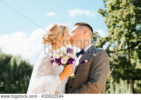 Portrait Of Young Beautiful Newlywed Couple Kissing In Park Outdoors, Groom Hugs Bride In White Dres