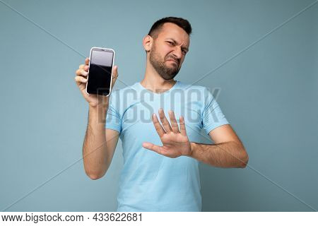 Sad Handsome Young Unshaven Brunet Man Wearing Everyday Blue T-shirt Isolated Over Blue Background H