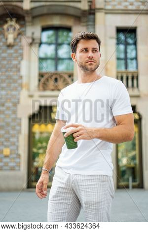 Modern Young Unshaven Brunet In Casual Summer Clothes Holding Disposable Cup Of Takeaway Drink While