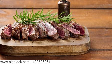 Fried Piece Of Beef Ribeye, Cut Into Pieces On A Brown Wooden Board, Rare Doneness